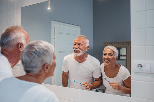 Mature couple brushing their teeth together in front of a bathroom mirror