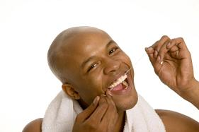 A man flossing his teeth to remove bacteria.
